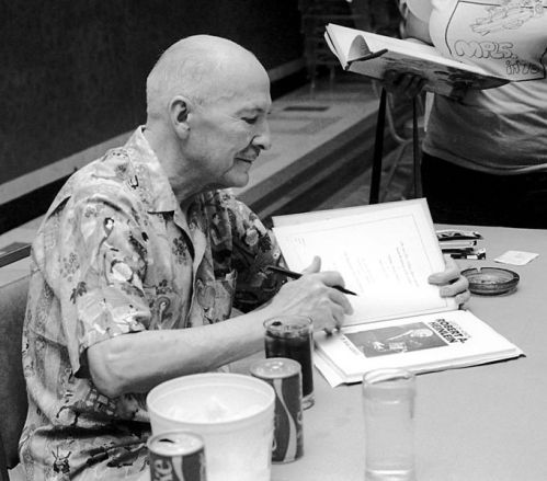 Novelist Robert A. Heinlein autographing one of his works.