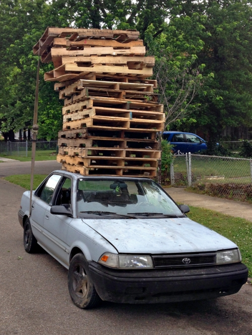 A stack of pallets that would be taller than the car if placed beside it.