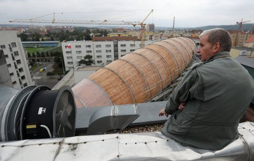 Leos Valka, a co-creator, sits on a rooftop overlooking a giant object resembling a zeppelin airship at an arts center in Prague, Czech Republic. The 42-meter long and 10-meter wide ship is planned to seat some 120 people on its cascade steps. It will be used for authors' reading and debates about literature to complement exhibitions at the DOX Centre for Contemporary Art, one of the most innovative and challenging galleries in the Czech capital. (AP Photo/Petr David Josek)